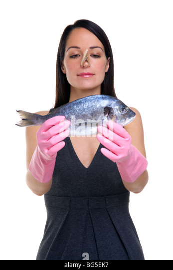 A woman wearing rubber gloves with a clothes peg on her nose holding a fish out in front of her, focus is on her - Stock Image