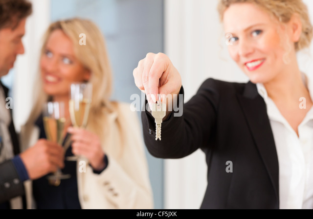Real estate market - young couple looking for real estate to rent or buy; they celebrate with champagne and get - Stock Image