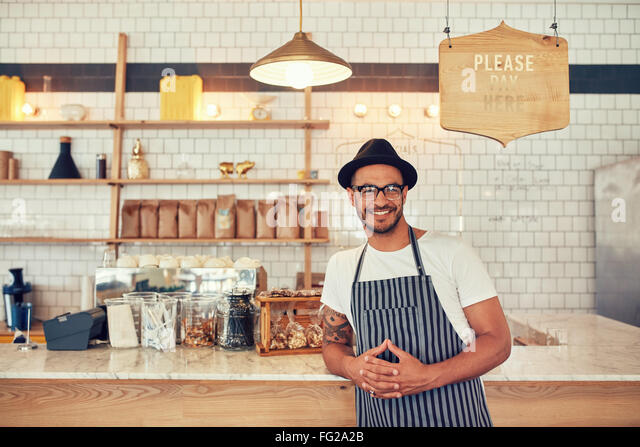 Portrait of happy young man wearing an apron and hat leaning to a cafe counter. Male barista standing at coffee - Stock Image