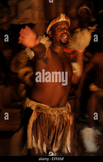 Male Zulu dancer in traditional costume with open arms Shakaland culture theme village KwaZulu-Natal South Africa - Stock-Bilder