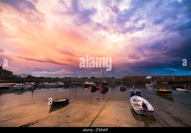 Mousehole, Cornwall, UK. 8th August 2017. UK Weather. As the sunset on the north west coast, Mousehole on the south - Stock Image