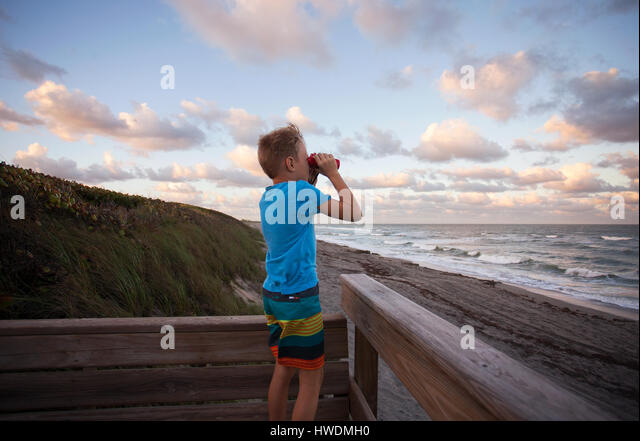 Boy at beach looking at view through binoculars, Blowing Rocks Preserve, Jupiter, Florida, USA - Stock-Bilder