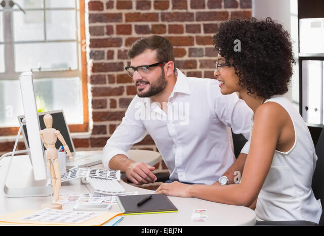 Photo editors using computer in office - Stock Image