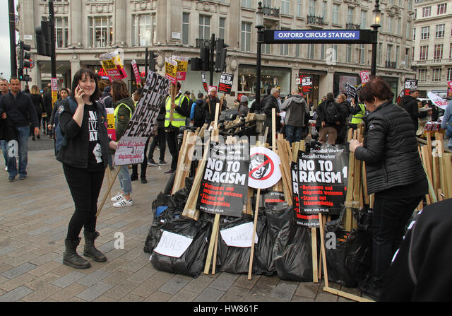 London, UK. March 18, 2017: A campaigner picks up  'No to Racism' placards by Oxford Circus station ahead - Stock Image