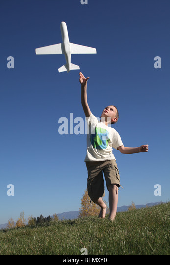 yhappy oung boy throwing toy airplane into the air - Stock Image