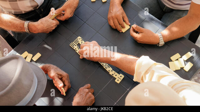 Retired people, seniors and free time. Old latino men having fun and playing game of domino in Cuba. High angle - Stock Image