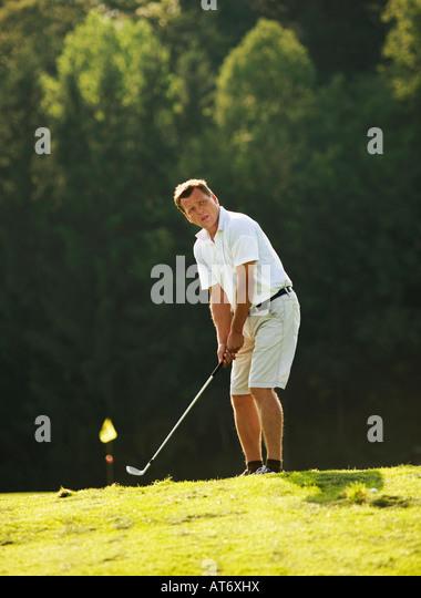 Austria, Male golfer swinging club on fairway - Stock Image