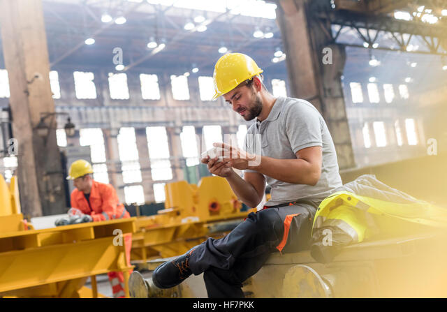 Steel worker texting with cell phone taking a break in factory - Stock Image