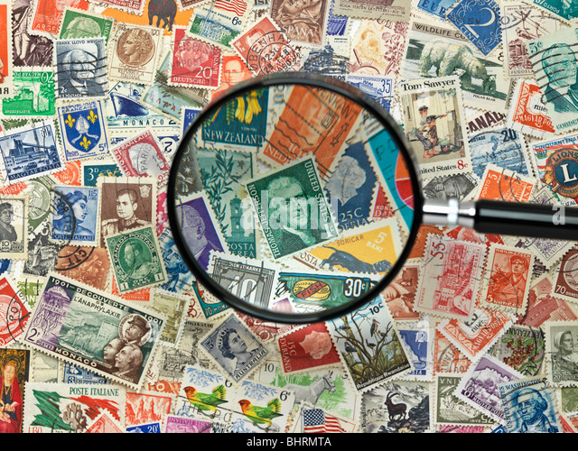 international postage stamps of the world with magnify glass - Stock Image