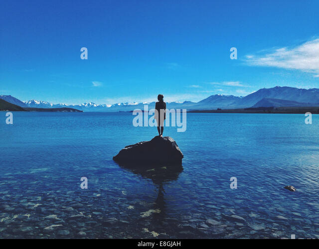 New Zealand, Canterbury, Lake Tekapo, Silhouette of woman standing on a large rock in a lake - Stock Image