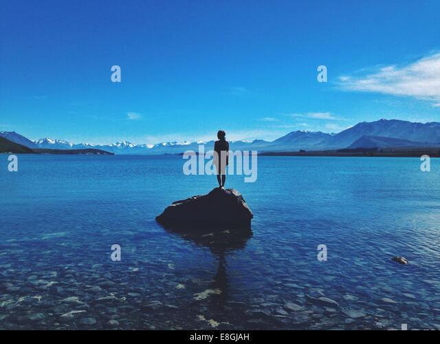 Woman standing on a rock, Lake Tekapo, Canterbury, New Zealand - Stock Image