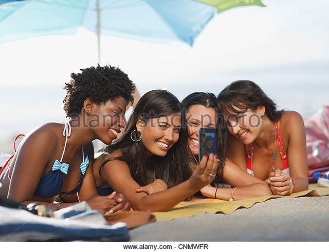 Women taking picture of themselves sunbathing - Stock Image