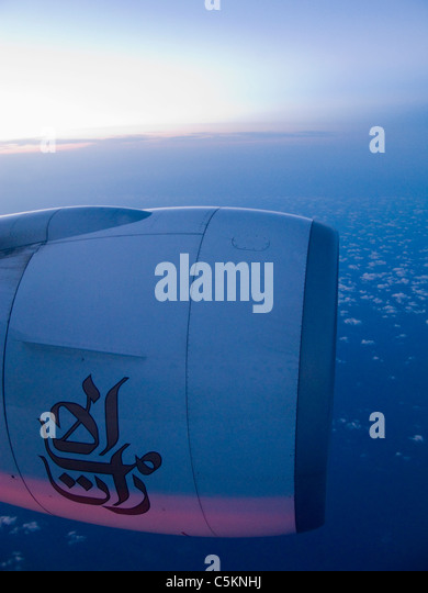 Port engine of a Boeing 777 jet airliner with logo of Emirates Airlines in flight at dusk - Stock Image