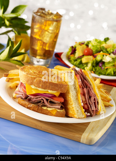 Gourmet roast beef sandwich served on grilled sourdough bread with french fries, a side salad and iced tea - Stock Image