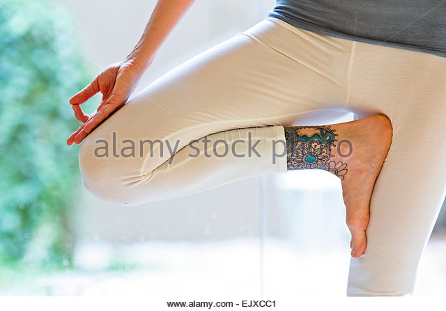 Woman Practicing Yoga, Tree pose, Low section - Stock Image