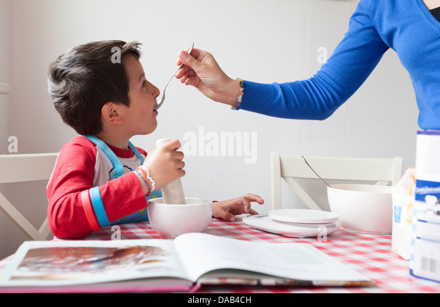 Mother and young son cooking together-food tasting - Stock Image