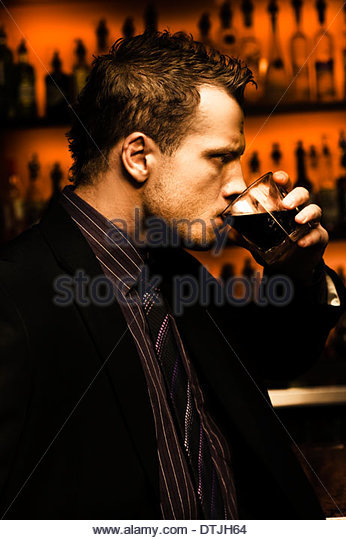 Rough And Tough Serious Male Drinker Downing A Glass Of Alcoholic Beverage Standing In Front Of A Bar - Stock Image