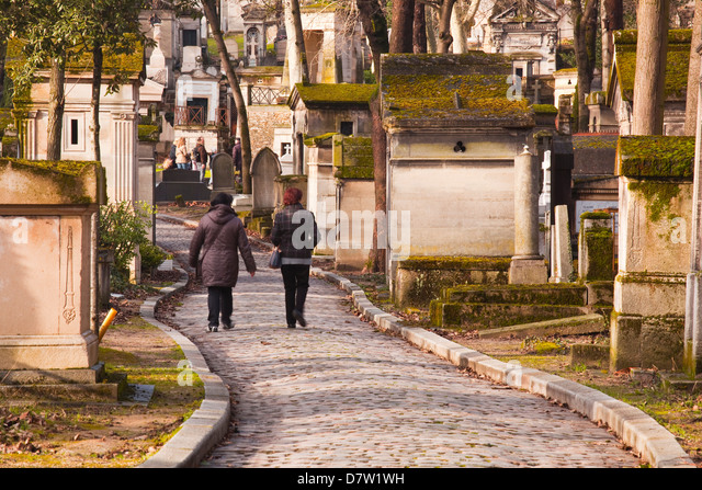 People walking past the gravestones of Pere Lachaise cemetery, Paris, France - Stock-Bilder