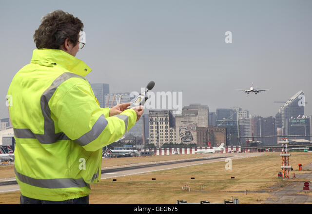 An environmental engineer monitors noise levels at London City Airport as plane lands. Canary Wharf in background. - Stock Image