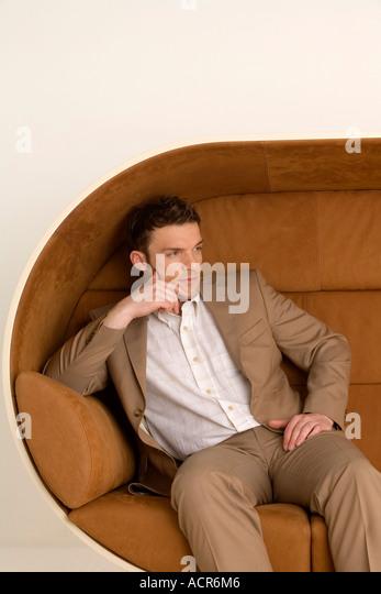 Businessman sitting on sofa, looking away - Stock Image