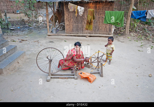 Woman spinning silk on home made spinning wheel made from wood and bicycle wheel, in rural village, West Bengal, - Stock Image