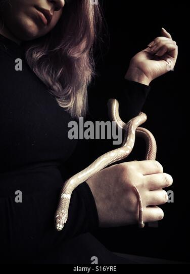 A teenage girl holding a pet snake. - Stock Image