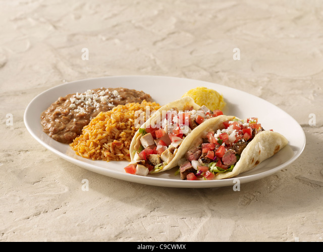 A fajita chicken taco and steak taco combo topped with salsa fresca and cheese and served with spanish rice and - Stock Image
