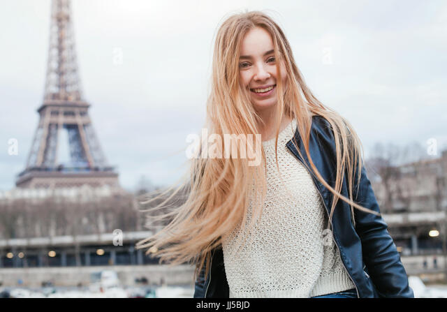 happy young woman in Paris near Eiffel tower, smiling girl traveling portrait, student in Europe - Stock Image