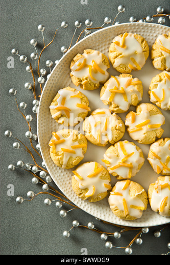 Orange Butter Cookies finished with orange zest icing on a grey holiday background. - Stock Image