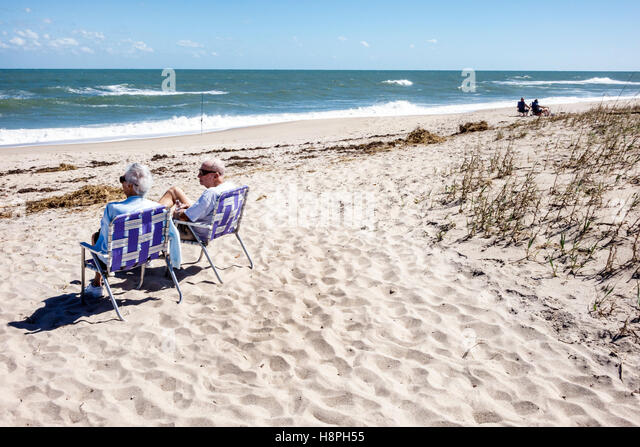 Vero Beach Florida Atlantic Ocean sand senior couple relaxing chairs - Stock Image
