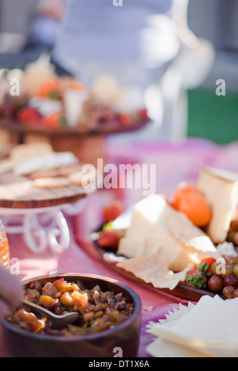 A table laid with a buffet selection of food dishes Desserts and cheese board - Stock Image