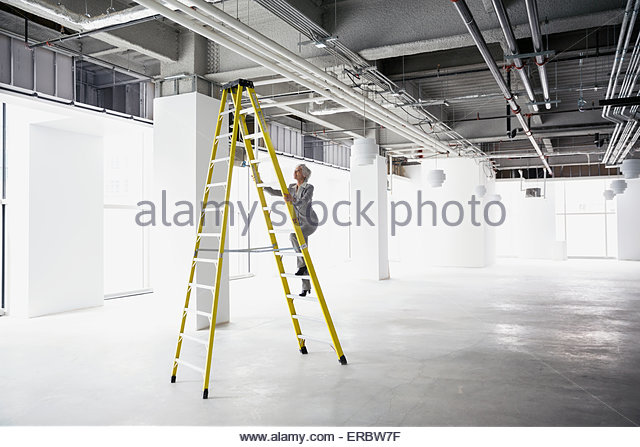 Businesswoman climbing ladder in empty office - Stock Image
