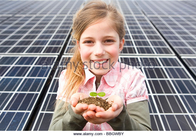 Young girl holding seedling and soil front solar panels Munich, Bavaria, Germany - Stock Image