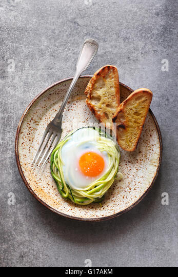 Breakfast with baked egg in zucchini noodles nest with bread toast on a ceramic plate - Stock Image