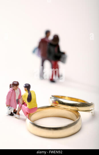 Concept image of a woman sat on wedding rings talking to a child to illustrate divorce the effects on children - Stock-Bilder