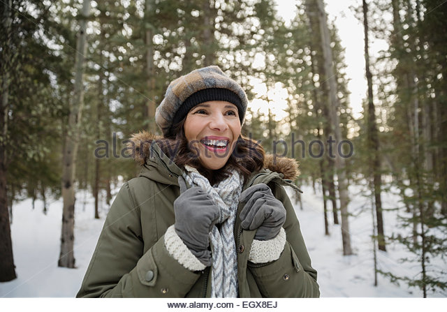 Smiling woman wearing warm clothing in snowy woods - Stock Image