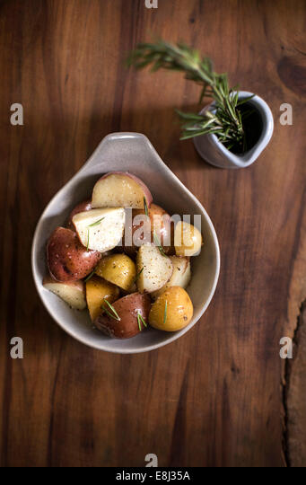 Bowl of seasoned red and white potatoes with jar of rosemary on dark wood tabletop. - Stock Image