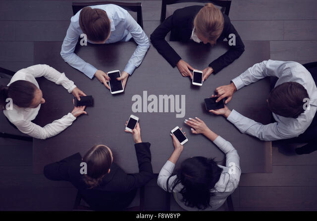 Business people with smartphones sitting around the table, top view - Stock Image