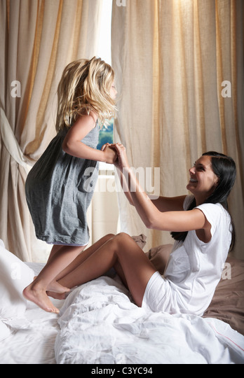 Mother and daughter playing on bed - Stock Image