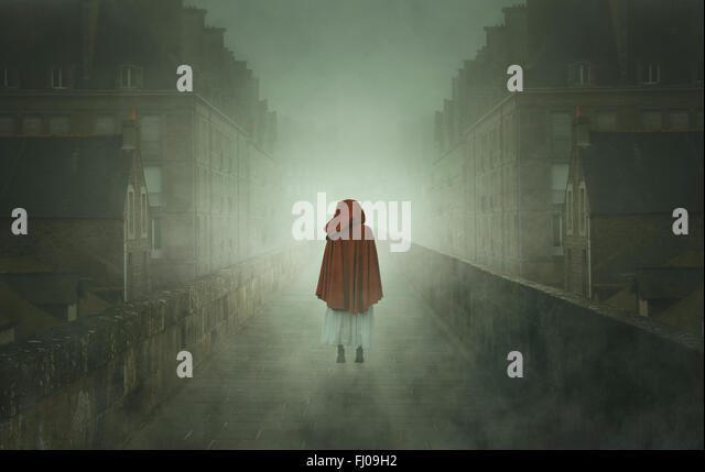 Mysterious hooded woman in a stone city. Weird and surreal - Stock-Bilder