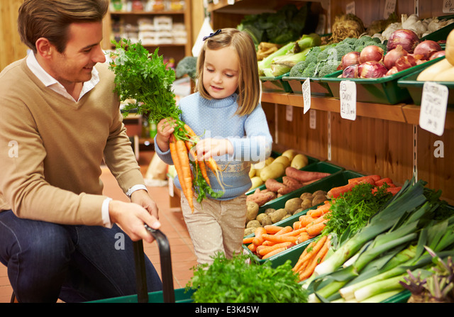 Father And Daughter Choosing Fresh Vegetables In Farm Shop - Stock Image