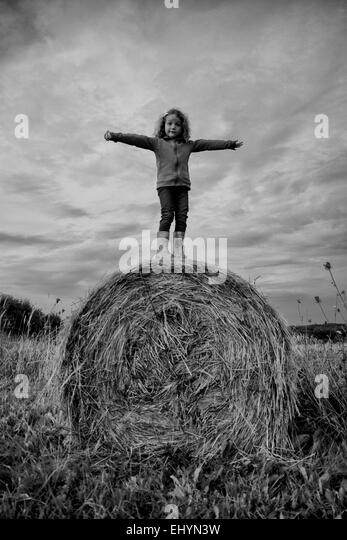Girl standing on a hay bale - Stock Image