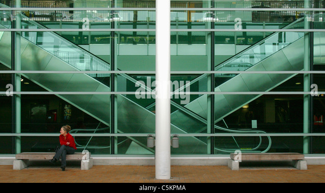 Two escalators (moving staircases) seen through green glass window, a woman in red top sitting on a bench outside, - Stock Image