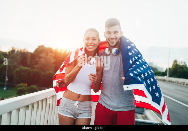 Portrait of attractive fitness couple holding American flag - Stock Image