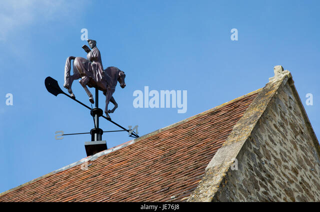 Canterbury Tales weather vane of Geoffrey Chaucer facing south reading a book while his horse heads north - at Hauser - Stock Image