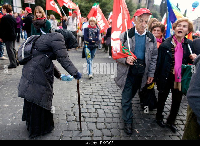 A woman begs for money as a political march passes her by in Rome, March 8, 2008. Photo/Chico Sanchez - Stock Image