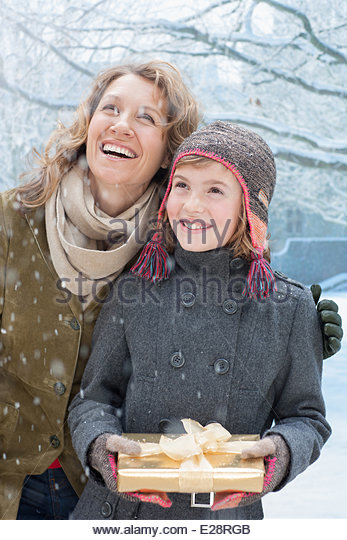 Mother and daughter holding Christmas gift in snow - Stock Image