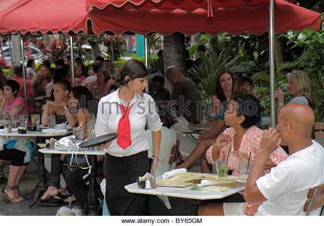 Miami Beach Florida Lincoln Road pedestrian mall dining shopping waitress Black woman man couple - Stock Image