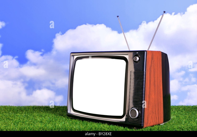 Photo of an old retro TV outdoors on grass with blue sky and white clouds in the background - Stock Image