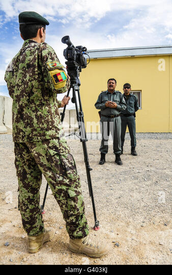 An Afghan National Army public affairs officer records an interview with police chief. - Stock Image